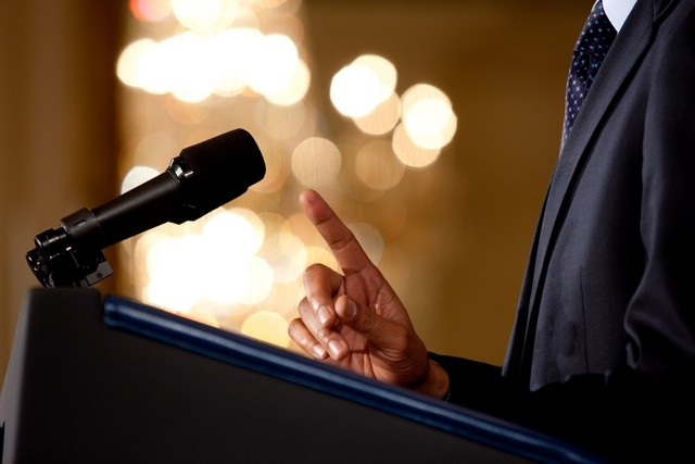 close_up_of_a_man_making_a_point_during_a_speech_microphone_and_podium_in_view_m